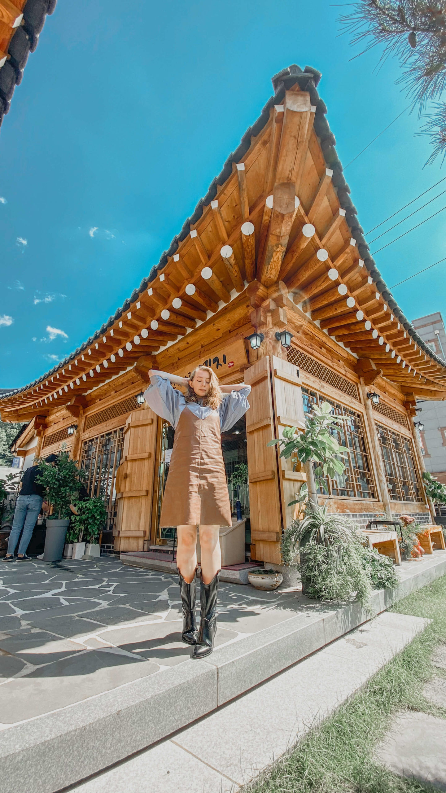 gongju outfit 3 - a photo of fii in front of a cafe in a modern hanok style building. she is wearing a blue blouse with large poofy  sleeves which is underneath a tan leather-look pinafore dress. She is wearing knee high cowboy botos