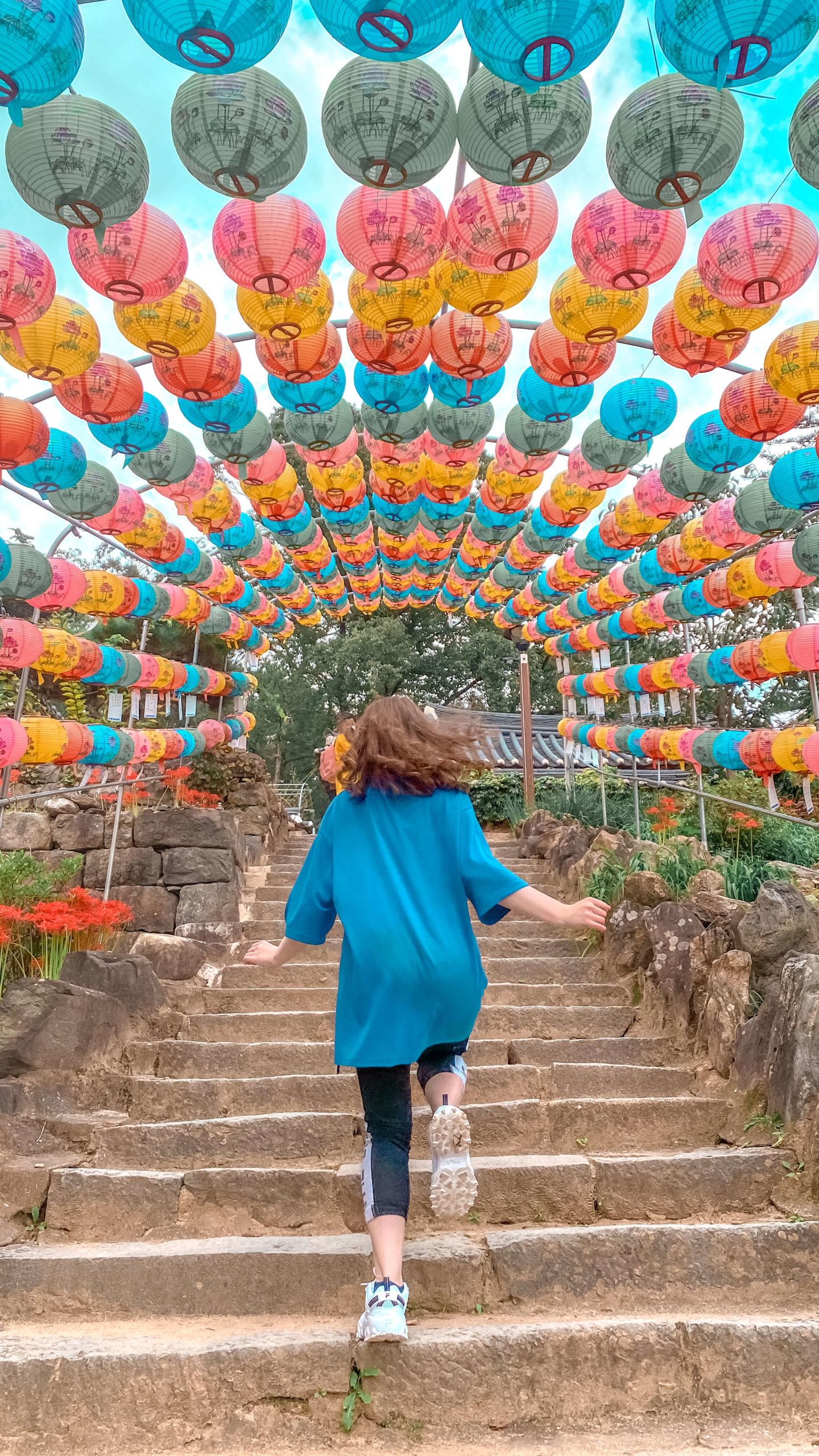 what I wore in Gongju city: fii running up stone steps in an easy comfy travel outfit of a light blue oversized t-shirt and workout leggings. Above the stairs are arches of multicoloured lanterns.
