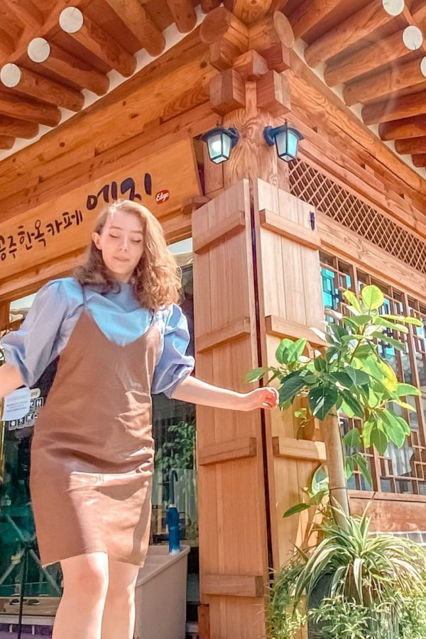 fii standing in front of a cafe in a building built in modern hanok style